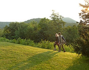 Couple walking grassy knob at The Swag, a Relais & Châteaux property